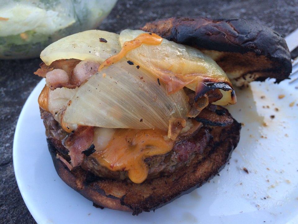 焼いたパンにハンバーグ、ベーコン、チーズ、たまねぎ、にんにく