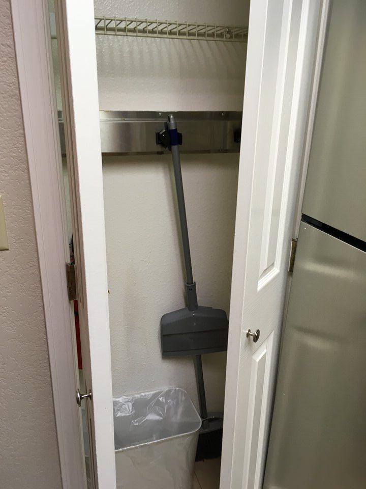 キッチン奥の扉にはホウキとゴミ箱