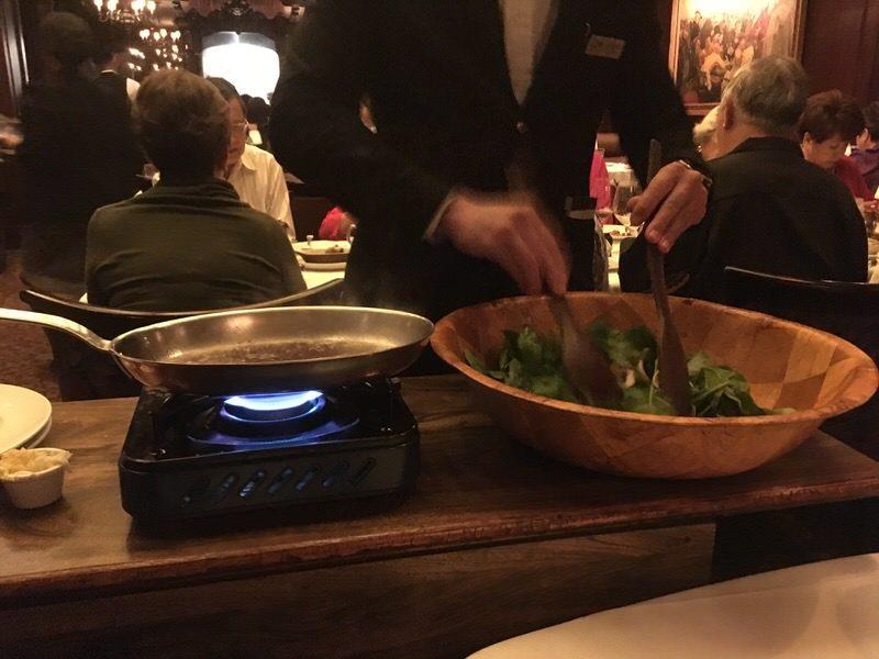 テーブルでサーバーが調理してくれる温かいほうれん草のサラダ